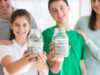 Proud parents watching children with college savings jars