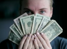 Girl holding cash on her hand in front of her face
