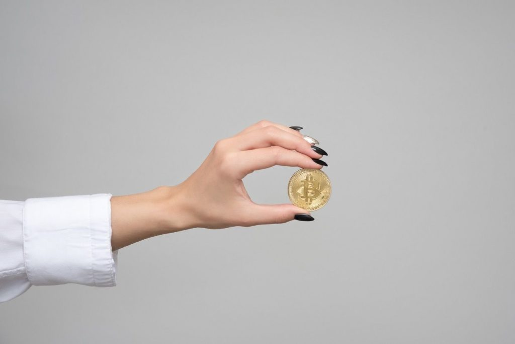 woman holding a bitcoin in her hand