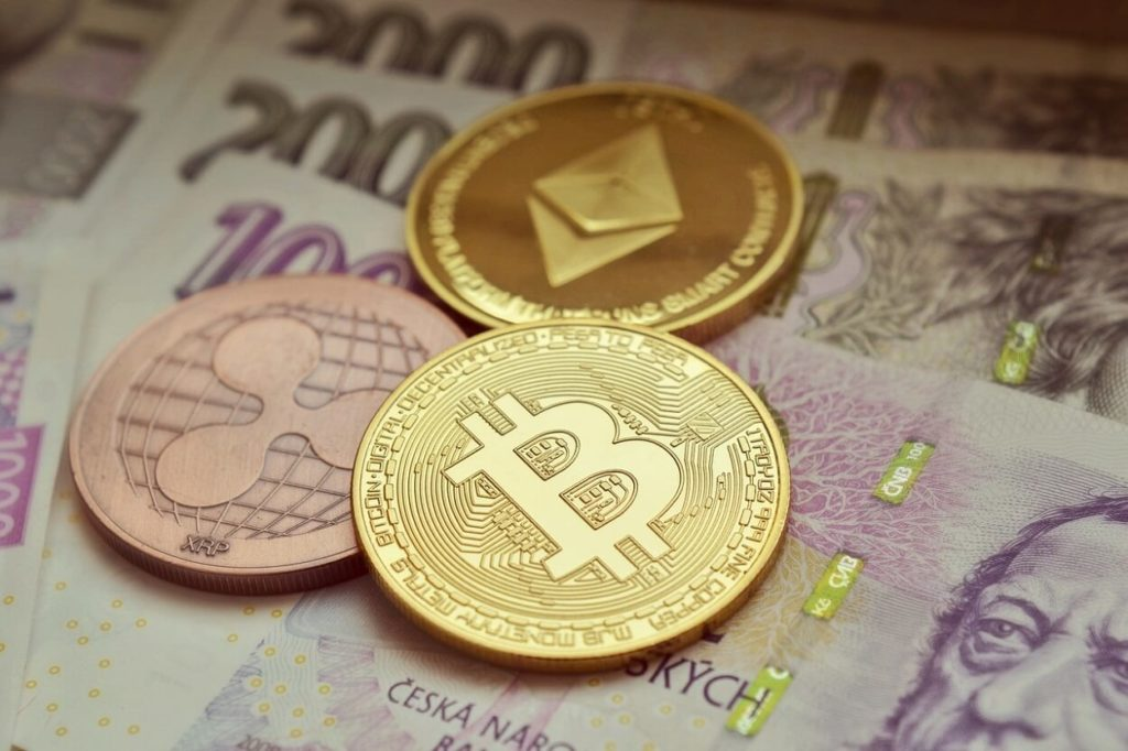 Different cryptocurrencies placed on currency notes